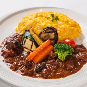 """新宿三丁目駅から徒歩2分ほどの距離にある「NIKKO KANAYA HOTEL CRAFT GRILL」。日本の名ホテルとしても有名な日光金谷ホテルの協力のもと、クラフト(=手作り)をコンセプトに、""""日本の洋食""""と""""クラフトリカー""""を提供しています。  本家の日光金谷ホテルにも負けない食べログの高評価を得ている人気店です。  こちらのオムライスは、さっぱりとしたバターライスにとろとろの卵ののったタイプ。牛すじたっぷりのハヤシソースがかかり、グリルされた彩りの良い野菜とともにアレンジされています。まろやかなハヤシソースは、シンプルなオムライスと馴染みよく、飽きずに最後までいただけます。"""