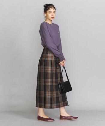 深みのあるブラウン系のチェック柄が大人の印象のキルトスカート。穿くだけで落ち着いた上品なイメージになるので、素足&ぺたんこパンプスであえて足元はハズして。