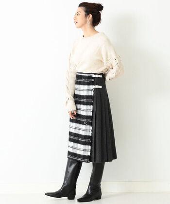 フロント部分はチェック柄、後ろは無地のユニークなキルトスカート。アイボリーのニットで上半身は優しい印象、足元はロングブーツでハードにした甘辛コーデです。