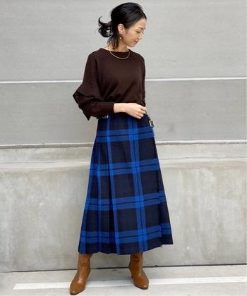 明るめのブルーのラインが印象的なロングキルトスカート。ブラウンのニット&ブーツで上品な大人のスタイルに。