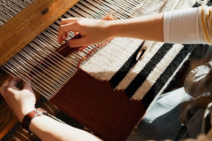 手織りとは、機織り機に縦に張り渡した複数の「タテ糸」に、横方向の「ヨコ糸」を入れて布を織り上げて交差をさせていく手工芸です。ヨコ糸は、杼(ひ)またはシャトルと呼ばれる道具に巻き付けて使います。