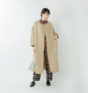 キルティング風の素材を使用し、コーデュロイのパイピングやくるみボタンでレトロな印象に仕上げたノーカラーコート。サイドには深めのスリットが入っているので、スカートにもパンツにもサッと羽織りやすい一枚です。両サイドに配置した大きなポケットも、ナチュラルコーデにぴったりなアクセントになっています。