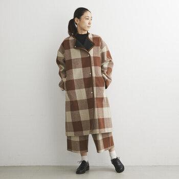 セミダブルシルエットで、ゆったりと着られるウール素材のチェック柄コートです。ボタンの開け閉めで、スタイリングを変えられるのが魅力。ノーカラーなので、大柄のコートもすっきり着こなせます。