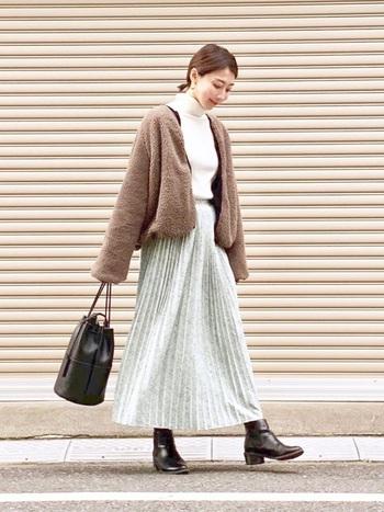 白のトップスに淡いカラーのプリーツスカートの組み合わせは、ともすると寒々しい印象になりがち。アウターにモコモコのボアアウターを持ってくることで、あたたかみのあるコーデに早変わり。小物を暗めのトーンでまとめると、メリハリの効いた着こなしになります。