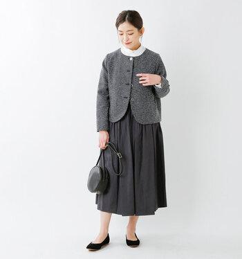 ミックスツイードが女性らしい印象を与える、グレーのクルーネックジャケット。白のフリルブラウスとグレーのフレアスカートに合わせて、シックながらも華やかさのあるフォーマルスタイルに仕上げています。