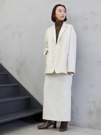 白のツイードジャケットに、同系色のロングタイトスカートを合わせた大人っぽいコーディネート。インナーにブラウンのハイネックニットをプラスし、ブーツも色を合わせて統一感を演出しています。