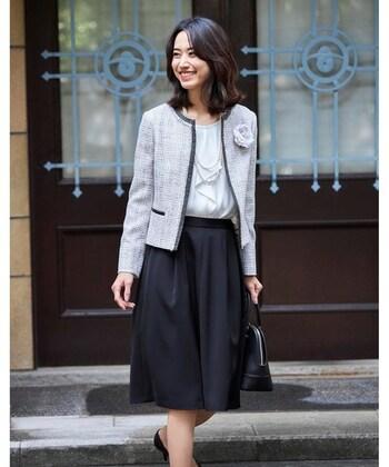 グレーのツイードジャケットに、白ブラウスとネイビーのひざ丈スカートを合わせたフォーマルコーデ。シックな印象のセットアップは、胸元にコサージュをプラスして華やかさをアップ♪