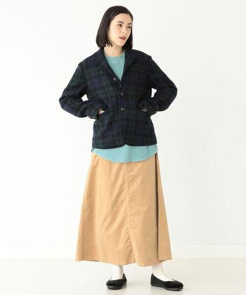 ハリスツイードの生地を使用した、エルボーパッチ付きのジャケット。ネイビー×グリーンのチェック柄に、薄いブルーのトップスを合わせて同系色でまとめています。ボトムスはベージュのロングスカートで、カジュアル×キレイめのミックススタイルに。