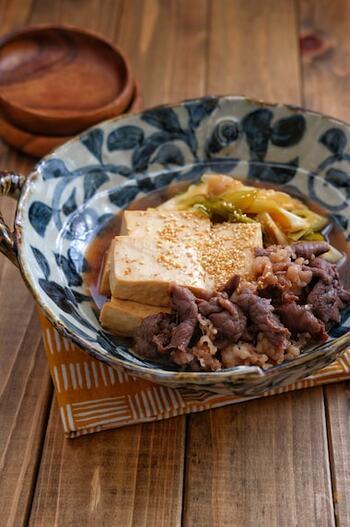 木綿豆腐を使ったベーシックな肉豆腐です。味がじっくり染み込みやすい木綿豆腐なら、お肉やネギから出る旨みをたっぷり吸ってくれますね。  一度、煮た後、すこし冷ますと味がより浸透していきます。食べるときにごまを擦って散らすと、香りよく、いただけますよ。