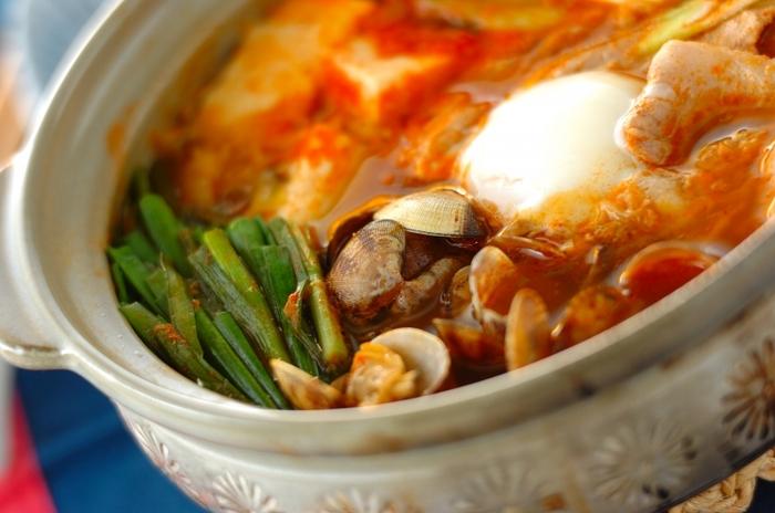 アサリと豚肉、ニラ、木綿豆腐、キムチをたっぷりと入れたチゲ鍋。アサリの出汁もたっぷり染み込んだ豆腐は、ピリリと辛いキムチ味とも好相性です。  具材に火が通ったら、温泉卵をトッピングすれば、とろりとまろやかな卵が全体を上手にひとつにまとめてくれます。
