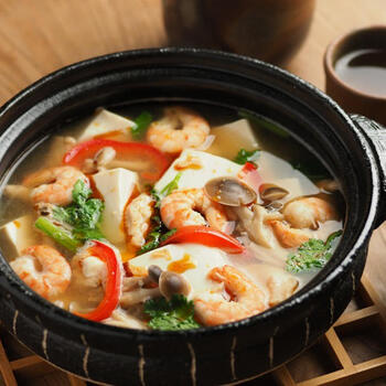 辛さと酸っぱさのあるトムヤムクン風スープをベースに、ラー油とライムで仕上げた豆腐鍋です。海老の旨みがじんわりと染みた豆腐はエスニックな風味によく合うんですよ。  殻付きの海老を煮ることで、風味と香りが抜群の出汁がとれます。海老は出汁がとれたら、いったん、取り出し、殻をむいてから再度お鍋に投入。これで豆腐と一緒に食べやすくなりますよ。