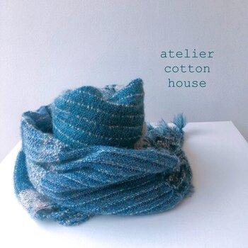 繊維の宝石カシミヤとベビーアルパカの糸で織られた贅沢なマフラー。手織ならではのやさしい風合いが魅力的で、暗くなりがちな冬のコートにきれいなブルーが良く映えます。