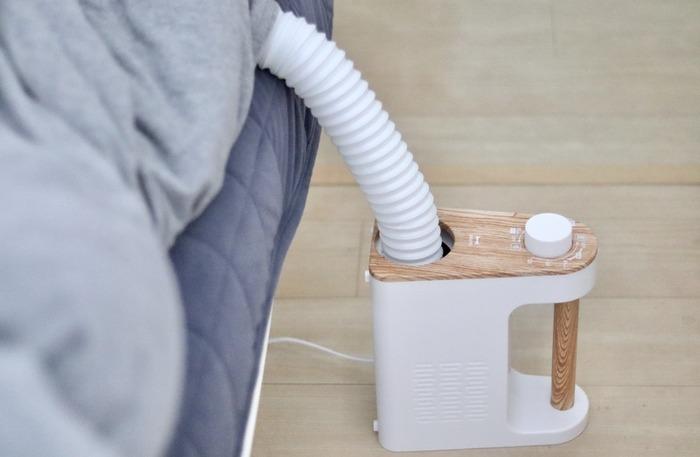 布団を干す作業は、なかなか大変ですよね。運んで干して取り込んで…と手間も多いものです。そんな布団干しの作業時間を軽減してくれるのが「布団乾燥機」ノズルを伸ばすだけで、ベッドに布団を敷いたまま乾かせるのでとっても手軽。ダニ予防もできます。天気や季節を問わずいつでもできるメリットも。