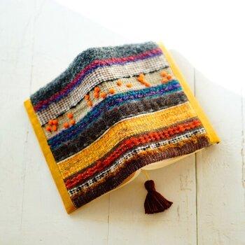 糸や織り方を変えながらの作った手織り生地のブックカバー。ウールやシルク、ファンシーヤーンなど、様々な種類の糸が使用され、とってもおしゃれな仕上がりです。本を持つ手も温かく心地よさも抜群。