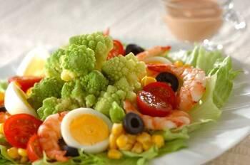 ライトグリーンのロマネスコに、トマトやエビの赤、コーンや卵の黄色にブラックオリーブ…、「映える」彩りの具だくさんサラダ。これ一品でテーブルがごちそう感で華やぎそう!