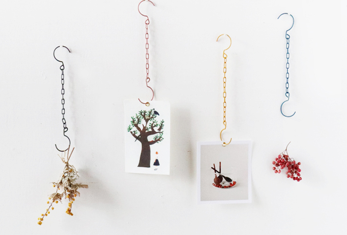 チェーンフックにポストカードを吊るして飾るアイデア。ポストカードに穴を開けて、ハトメパンチで金具を付けるとさらにおしゃれです。チェーンフックの材料も、ハトメパンチも100均で手に入りますよ。