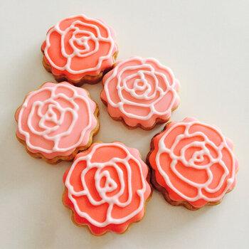 ベースにピンク色のアイシングをべた塗し、白のアイシングクリームでエレガントな薔薇のデザインを描いています。花びらの重なるように描くのがポイントです。
