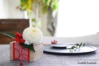 升の中にココットを入れて、ピンポンマム・南天・千両を生けています。手のひらサイズなので卓上にも飾りやすい。テお正月の食卓にモダンな華を添えてくれます。