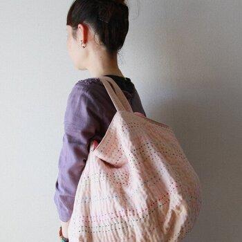 見た目もやさしい淡いピンクの4重ガーゼの生地に、様々な色の糸を刺した、かわいらしいバッグ。優しい雰囲気ながらも、シンプルな装いに映える素敵な風合いです。