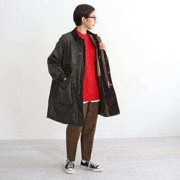 ブラウンのチェック柄パンツに、赤ニットを合わせたスタイリング。黒のアウターとスニーカーで、メンズライクにまとめています。ニットの裾から少しだけ白インナーを覗かせて、さりげなくレイヤード感をアピールしています。