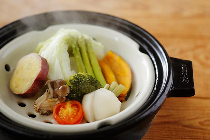 """土鍋で楽しみたい料理のひとつが「蒸し料理」。野菜の栄養を余さずいただく調理法は""""蒸し野菜""""にすること。こちらの土鍋は、そんな蒸し料理を気軽に楽しめる陶製すのこが付属されていて便利。土鍋に付属して陶製すのこを持ち上げるステンレス製のトングが付いています。蒸し鍋のレシピ付きなので、新しい料理のレパートリーがどんどん増えそうですね。"""