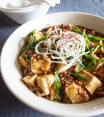 生姜、にんにく、ねぎ、甜麺醤で香りを立たせた麻婆豆腐です。白髪ねぎ、花椒粉、万能ねぎ、糸唐辛子をトッピングすると、本格的な雰囲気に。辛みを足したいときは、甜麺醤と一緒に豆板醤を入れましょう。  おうちで作る麻婆豆腐は家族構成によって、辛みを調整できるのがいいですよね。