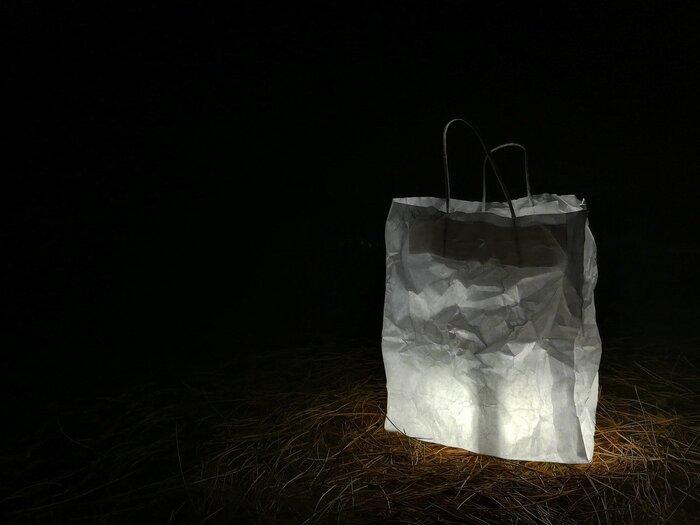 """【必要なもの】 1.懐中電灯orスマホのライト 2.水の入ったペットボトルorレジ袋(白)  手順は簡単。気球のように見立てたレジ袋の中にライトを入れるだけ。ペットボトルの場合はライトの上に乗せるだけです。レジ袋はビニールが一般的ですが、画像のように紙袋でも代用ができますよ。  ペットボトルの水には極少量、牛乳を混ぜてあげると""""チンダル現象""""により光量を増してくれます。同じように袋も白色を選ぶのがベストです。"""