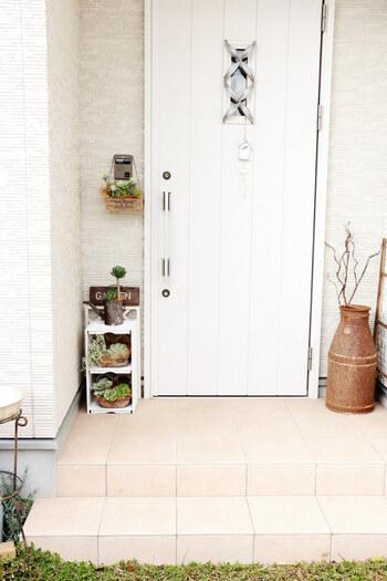 白で統一された壁材・ドアにさりげないアクセントが施された玄関周り。棚やグリーンやツリーが無機質なモノトーンにナチュラルなアクセントを添えています。