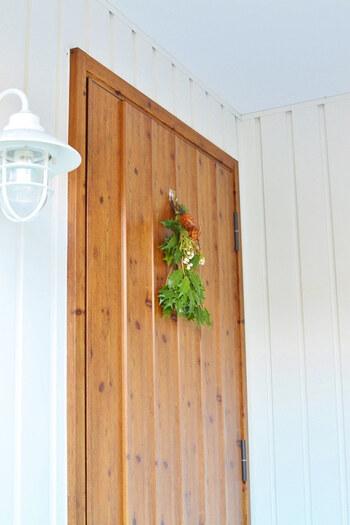 節分に魔除けとして用いられる柊のドア飾り。本来は鰯を添えた「柊鰯(ひいらぎいわし)」を飾りますが、手軽さとインテリア性を考慮して、柊のみで飾り付けされています。木目の扉とホワイトの壁に、柊の緑がよく映えますね。