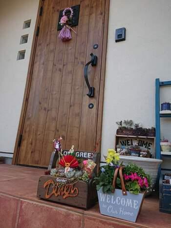 玄関前のプランターに、小さな門松やお正月飾りを添えるアイデア。少しの工夫でしっかり季節感が出せています。ピンクのドア飾りも相まって、かわいらしい玄関に。