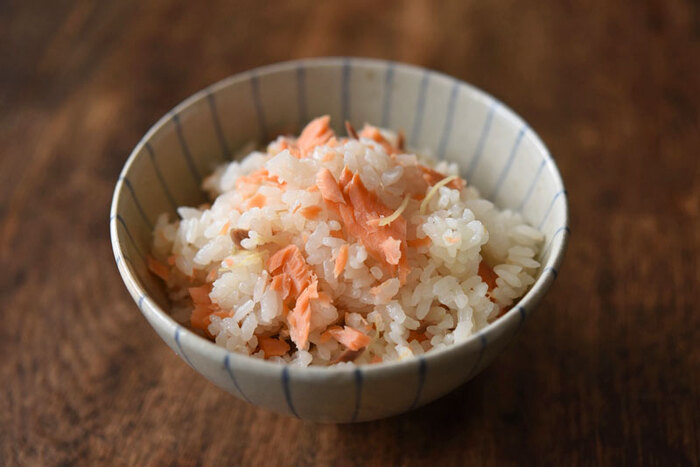 塩鮭を使った炊き込みご飯のレシピです。鮭の切り身とご飯を一緒に炊き、炊けたら鮭だけ取り出して骨や皮を覗いてからご飯に混ぜるので、塩鮭を焼く手間をカットしています。おにぎりにしてお弁当に入れるのもおすすめです。