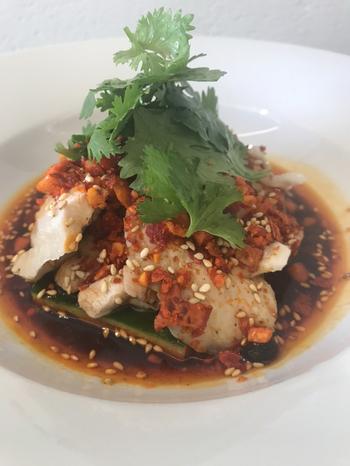 """「よだれ鶏""""REI""""スタイル」はシェフの故郷である山梨の信玄鶏を使った一品。辛さは控えめなので、しっかりと食材の味を堪能できます。"""