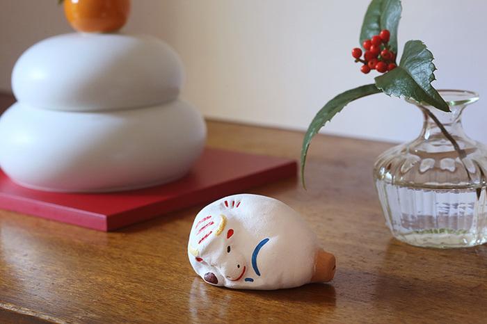 土の表情が感じられる素朴な土人形の丑です。真っ白に塗られた白地が上品な印象もあって不思議な魅力があります。鮮やかに引かれた色が縁起物らしい華やかさを生んでいますね。素地の部分は吹き口になっていて、笛として鳴らせて遊ぶこともできます。