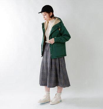 グリーンのボアパーカーに、グレーのスカートを合わせたコーディネートです。足元は白のスニーカーで、カジュアルガーリーなテイストに。こちらの着こなしは靴下を合わせていますが、寒さを感じる季節にはタイツなどをプラスしても◎