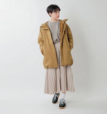 ベージュのダウンコートに、トーン違いのベージュカラーを合わせたコーデ。カジュアルなアウター&シューズの着こなしですが、プリーツスカートを合わせるだけでグッと女性らしい印象になりますね。
