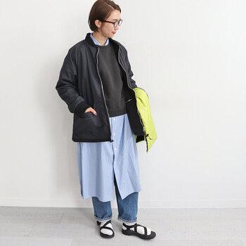 メンズライクな黒のフリースジャケットに、ストライプのシャツワンピースを合わせたコーディネートです。ワンピースの上にニットを重ねて、キレイめなレイヤードコーデに。足元は白靴下×サンダルで抜け感をプラスしていますが、冬コーデならショートブーツを合わせるのもおすすめです。