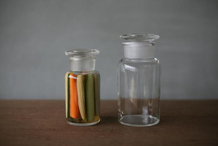小泉硝子製作所の広口試薬瓶はレトロな趣があって、自家製のピクルスや甘夏のシロップ漬けなど色のきれいなものを入れておくのにぴったり。すぼまった口のすりガラス部分が美しいアクセントになっていますね。  丸みをおびた肩のラインに光が反射して、並べておくだけでもお洒落なインテリアに。いくつか同じものを並べれば、まとまりのあるエリアを作れますよ。