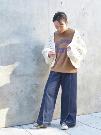 白いざっくり編みの可愛らしいボレロには、あえてカジュアルなテイストのアイテムを合わせて。ロゴ入りのトップスやスニーカーで仕上げれば、カジュアルだけど優しさもある着こなしに。色味でコントラストを強めてメリハリを。