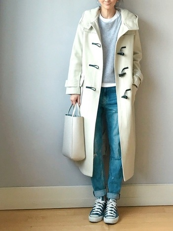 ダメージジーンズにグレーのニットというカジュアルなコーデ。ホワイト系のダッフルコートを合わせると上品な雰囲気に。