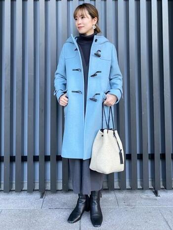 ダークな冬の街にパッと映えるライトブルーのコート。コートを主役にするために、他のアイテムは色を抑えめにします。