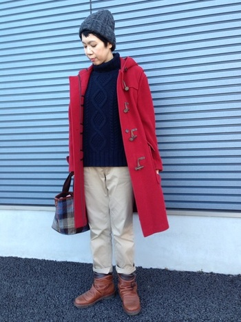 ネービーのニット&ベージュのチノパンというトラッドなコーデ。赤のコートで遊び心を演出して。