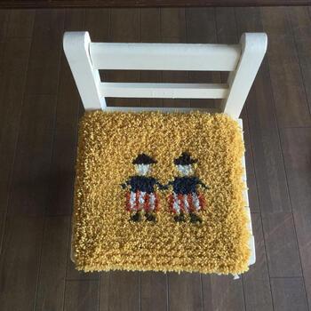かわいらしい子供が描かれた椅子敷きのキットです。図案とヨコ糸、ラグウールなどがセットになっています。作り方の詳しいテキストや木枠などの材料は別売りなので、必要に応じて買い足します。