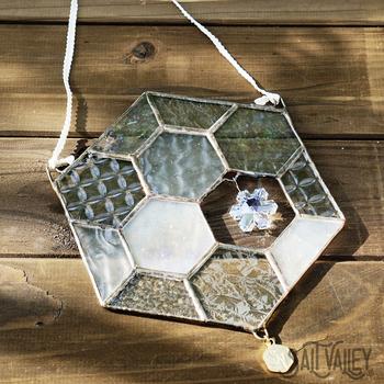 雪の集まりを表現したハニカムデザインのサンキャッチャーは、中央にあしらった雪の結晶のようなクリスタルガラスがワンポイント。パネルには異なる模様のガラスが数種類使われており、太陽の光に反射してお部屋を優しく照らしてくれそうです。