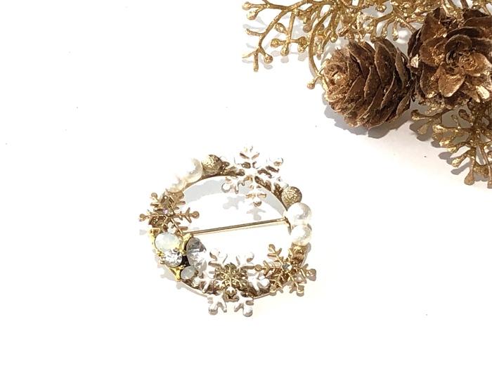 ゴールドの台座に雪の結晶パーツをあしらった、エレガントなリングブローチ。雪の結晶の中心の小さなスワロフスキーと散りばめられたビジューが、光に反射してキラキラと美しく輝きます。