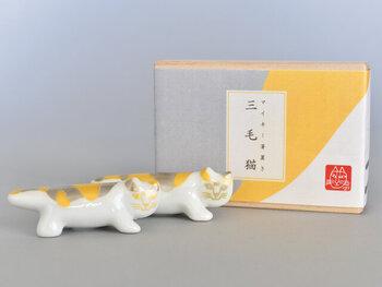 こちらは金と銀の染付けが施されたなんともおめでたい雰囲気の三毛猫柄の箸置き。一点一点職人さんの手により仕上げられているため、よく見ると顔の表情が異なります。木箱に入っているので猫好きな方へのギフトにも喜ばれそう!