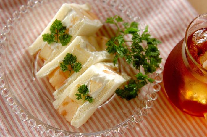 水切りヨーグルトをクリームチーズ風に使ったフルーツサンド。こちらでは桃を使っていますが、旬のものや好きなフルーツでアレンジしても◎メープルシロップでほんのり甘味をつけ、フルーツのおいしさを感じられるサンドイッチです。