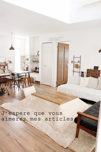 こたつのカラーは、ご自宅のフローリングや壁の色や家具の質感などに合わせるとインテリアに統一感が出ます。 例えば、床や壁が白やナチュラル系の明るめのカラーなら、ラグやこたつ布団も同系色のベージュやオフホワイトにすると、圧迫感がなくなり、お部屋が広く見えますよ。  こちらのリビングでは、お部屋全体を淡いトーンでまとめつつ、ダークカラーのソファやオブジェが空間を程よく引き締めています。