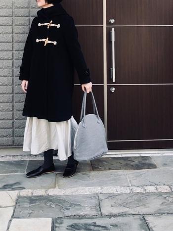 二つの留め具が印象的なコートは、デザインがとっても素敵。コートをたっぷりと満喫するなら前を留めて着こなしましょう。コートとカラーが真逆の黒のスカートが、コートをしっかりと引き立てているのでバランスの良いコーデになっています。