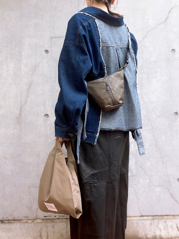 デニムとレザースカートのメンズライクなコーデに、カーキのショルダーバッグとベージュのエコバッグを合わせて。2つのバッグがコーデの差し色にもなっています。
