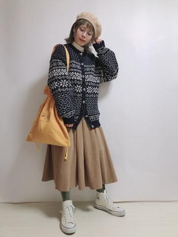 ベージュのスカートにホワイトのスニーカーという優しい色味の組み合わせを壊さないように、グリーンのタイツで中和させて。